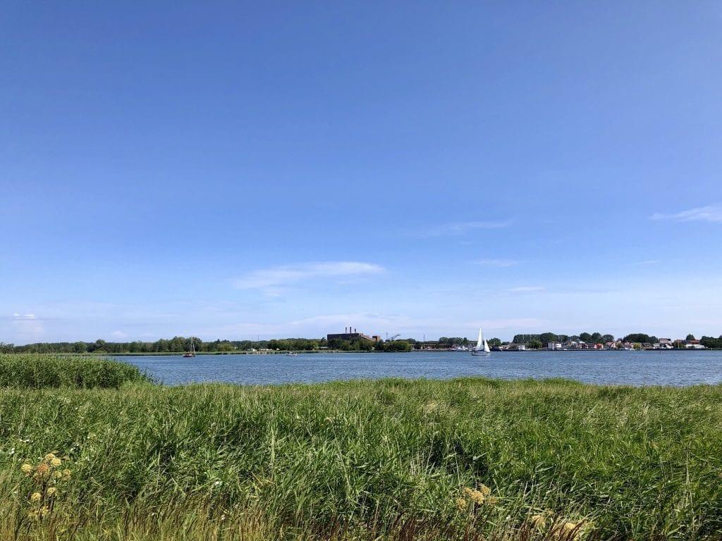 Blick über den Peenestrom nach Peenemünde auf Usedom, rechts der Hafen, in der Mitte das alte Kraftwerk
